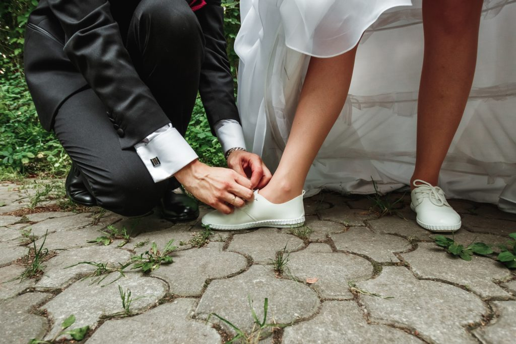 Submissive man ties up the bride's shoes